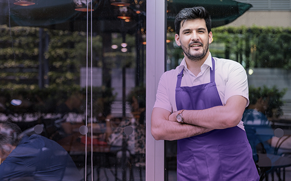 Man in apron standing outside restaurant.
